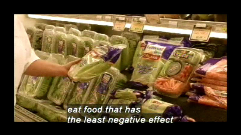 Person holding a package of lettuce while standing in front of shelves of produce. Caption: eat food that has the least negative effect