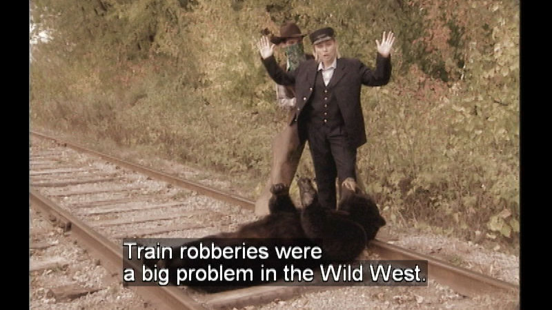 A bear laying across train tracks with two people standing above it. Caption: Train robberies were a big problem in the Wild West.