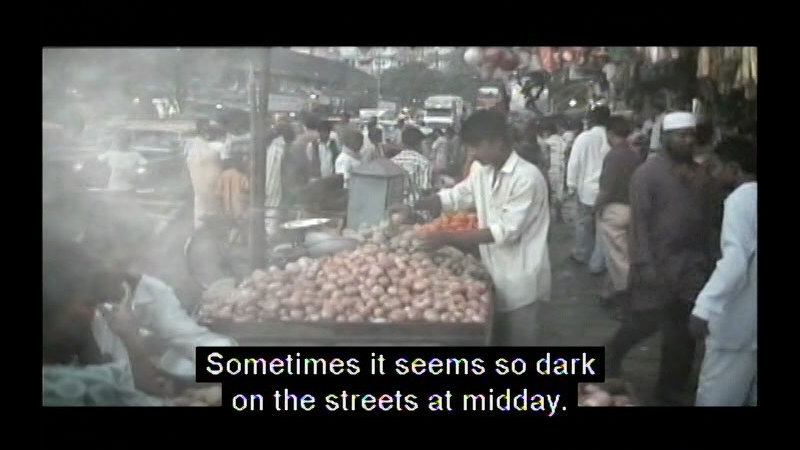 A crowded street covered in fog. Caption: Sometimes it seems so dark on the streets at midday.
