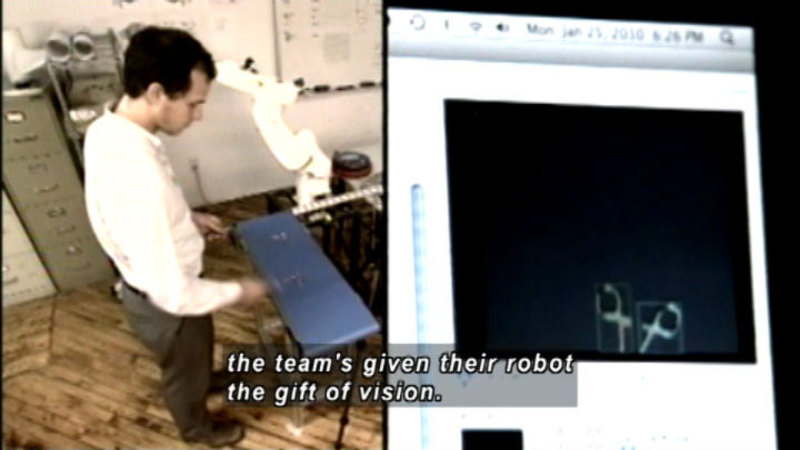 Person standing and working on something at waist level. Image of a computer screen. Caption: the team's given their robot the gift of vision.
