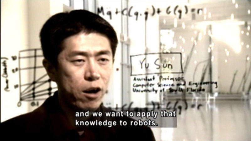 Person speaking. Behind them is a graph, mathematical equations, and writing. Caption: and we want to apply that knowledge to robots.