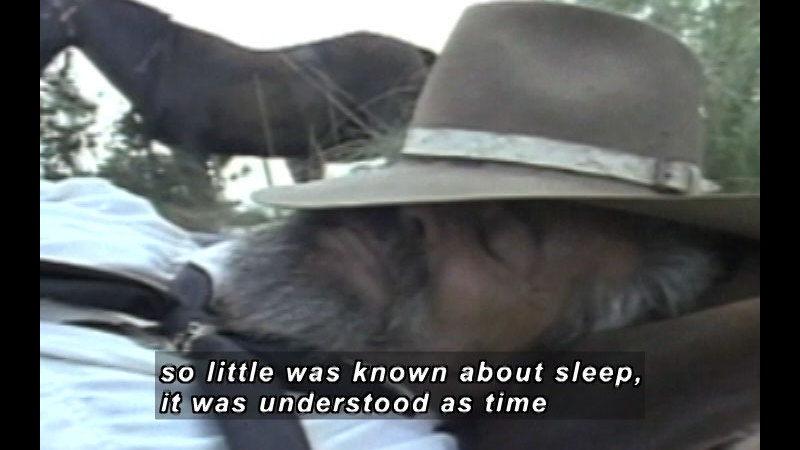 A man sleeping with his face covered by his hat. Caption: so little was known about sleep, it was understood as time