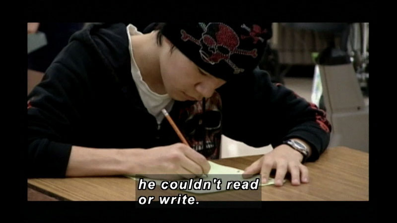A teenager wearing a beanie with skull and crossbones and a hoodie with a skull, sitting at a desk and writing on a piece of paper. Caption: he couldn't read or write.