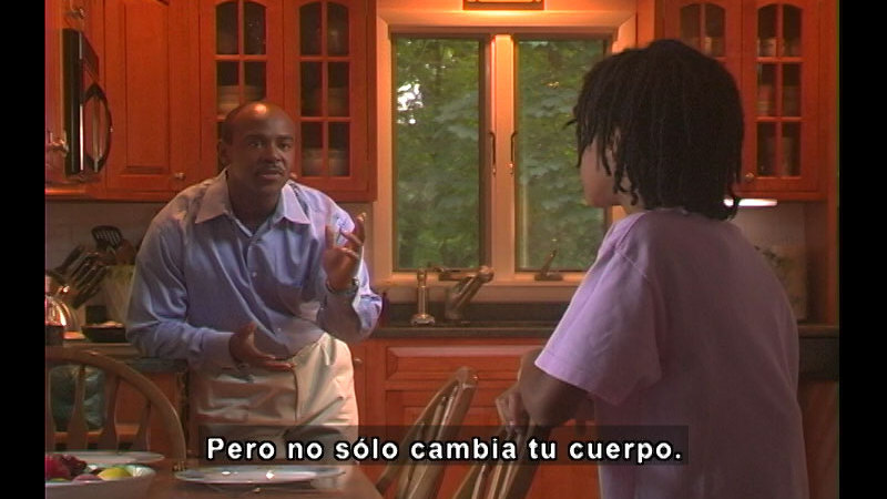 Adult and young person talking in a kitchen. Spanish captions.