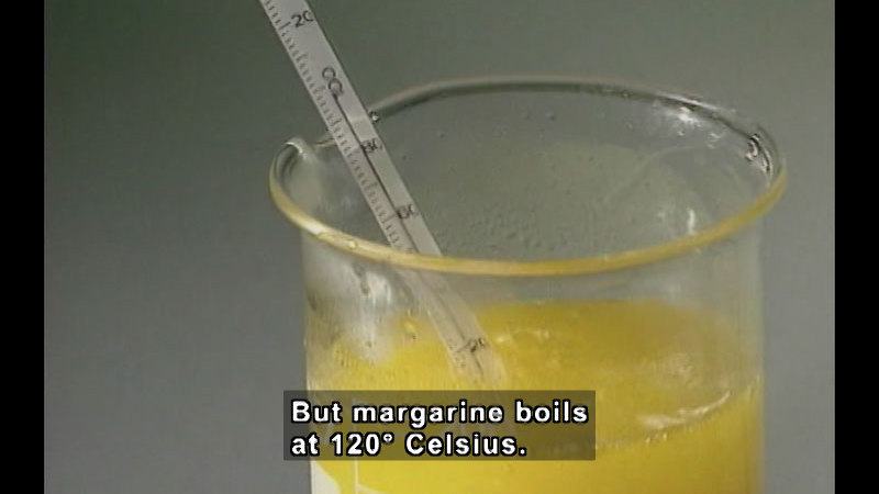 Thermometer in a beaker of boiling yellow fluid. Caption: But margarine boils at 120 degrees Celsius.