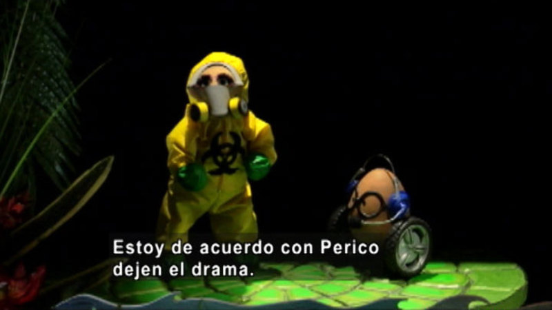 Two puppets, one in a hazmat suit.  Spanish captions.