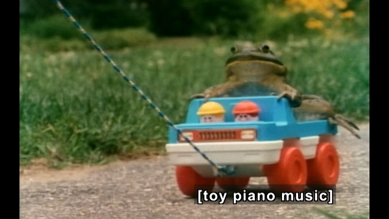 A frog riding on a toy truck being pulled on a string. Caption: [toy piano music]