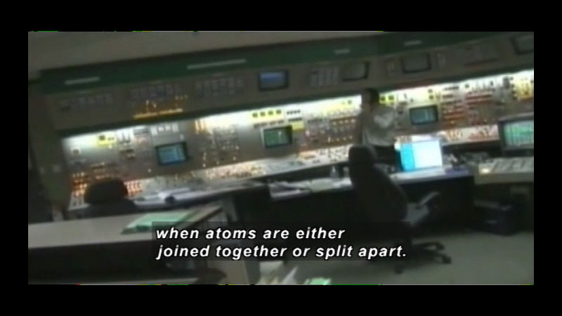 Person at a wall of controls. Caption: when atoms are either joined together or split apart.