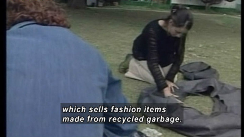 Person kneeling on the ground next to a pile of dark material. Caption: which sells fashion items made from recycled garbage.