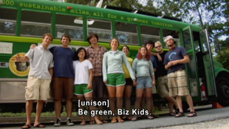 10 people standing closely together in front of a school bus painted green. Caption: [unison] Be green, Biz Kids.