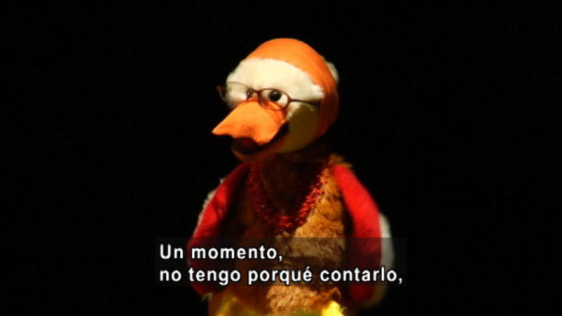 A bird puppet wearing glasses. Spanish captions.
