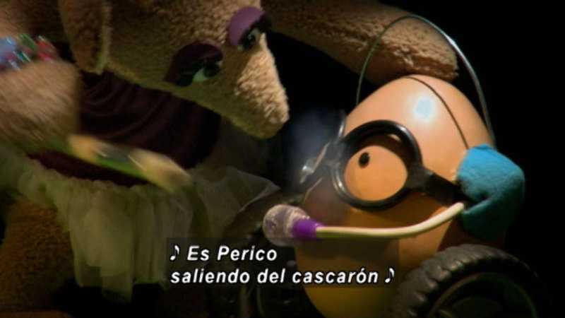 Two puppets talking to each other. Spanish captions.