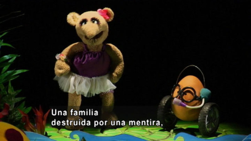 A girl puppet talking to another puppet. Spanish captions.