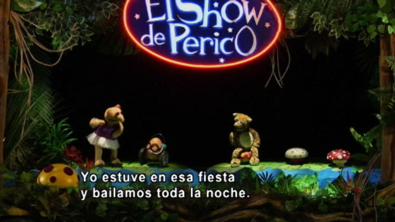 Three puppets on a stage. Spanish captions.