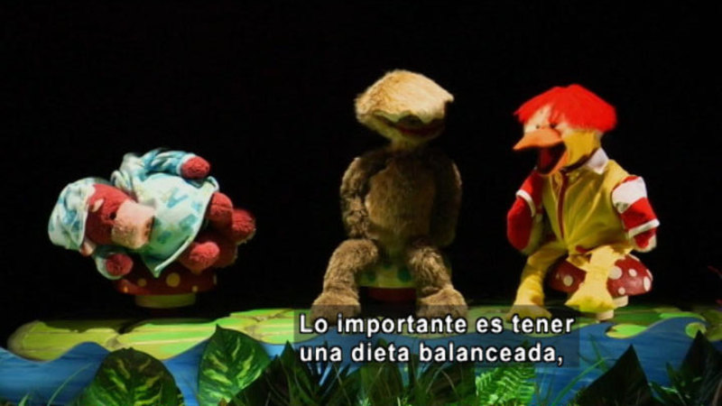 Three puppets talking by the water. Spanish captions.