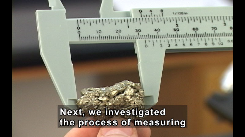 Hand holding a small shiny piece of metal being measured with a ruler. Caption: Next, we investigated the process of measuring