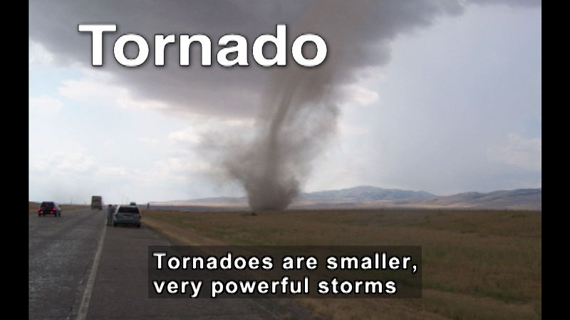 Vehicles driving on a road with a funnel-shaped cloud descending from the sky. Caption: Tornadoes are smaller, very powerful storms