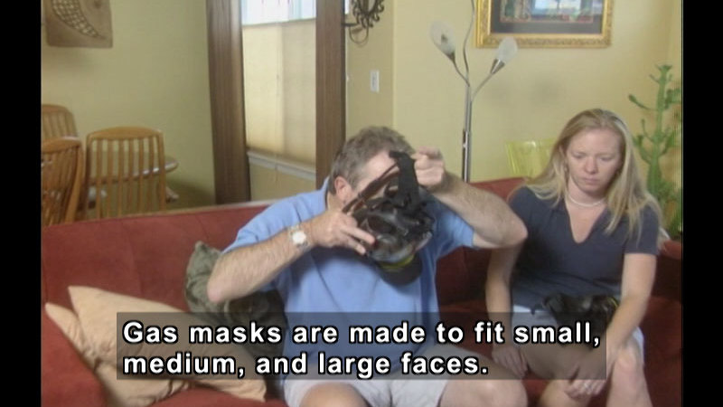 Two people sit on a couch. One is putting on a gas mask. Caption: Gas masks are made to fit small, medium, and large faces.