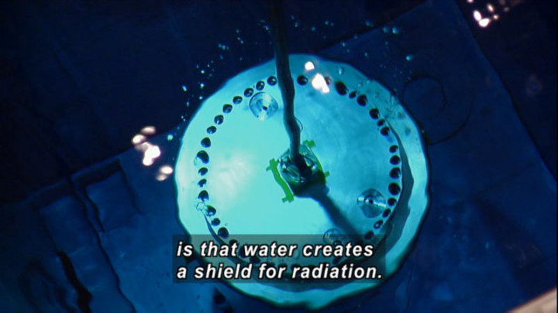Round metal object underwater. Caption: is that water creates a shield for radiation.