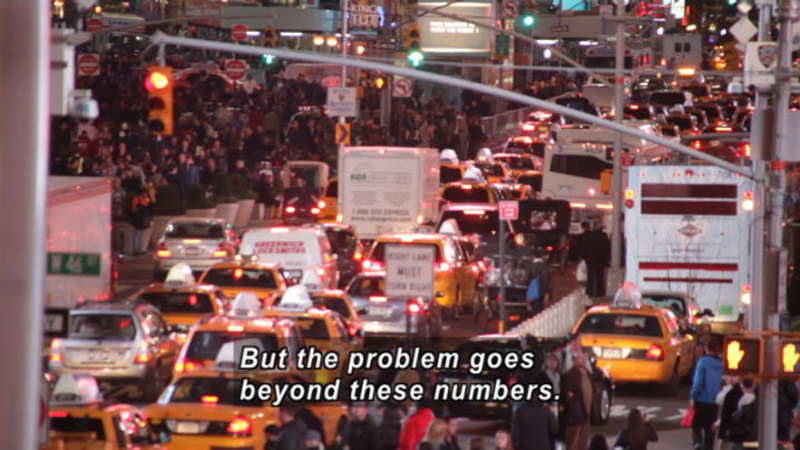Extremely busy city street full of vehicles and people. Caption: But the problem goes beyond these numbers.