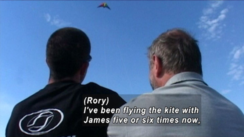 Two people looking up at a kite flying in the sky. Caption: {Rory) I've been flying the kite with James five or six times now,