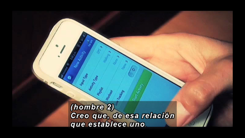 Person holding a smart phone. Spanish captions.