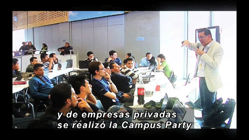 Teacher speaking in front of a lecture hall full of students. Spanish captions.