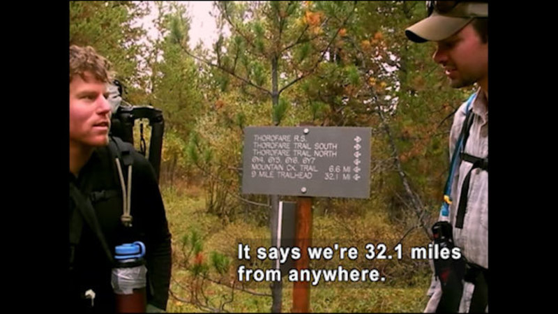 Two people in hiking gear standing next to a sign showing destinations and distance. Caption: It says we're 32.1 miles from anywhere.