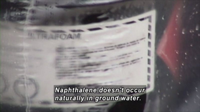 Blurry product label as seen through clear film. Caption: Naphthalene doesn't occur naturally in ground water.