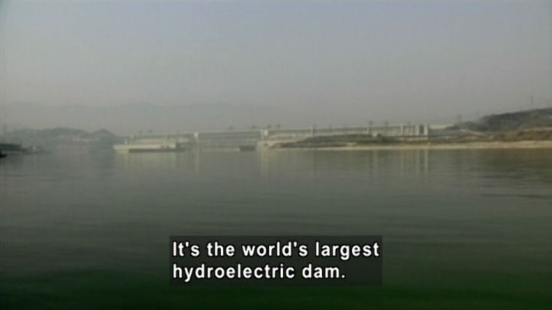 A large dam spanning across a lake. Caption: It's the world's largest hydroelectric dam.