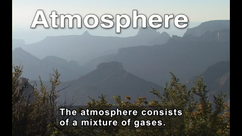 Treetops in the foreground and rolling mountains in the distance. Caption: The atmosphere consists of a mixture of gases.