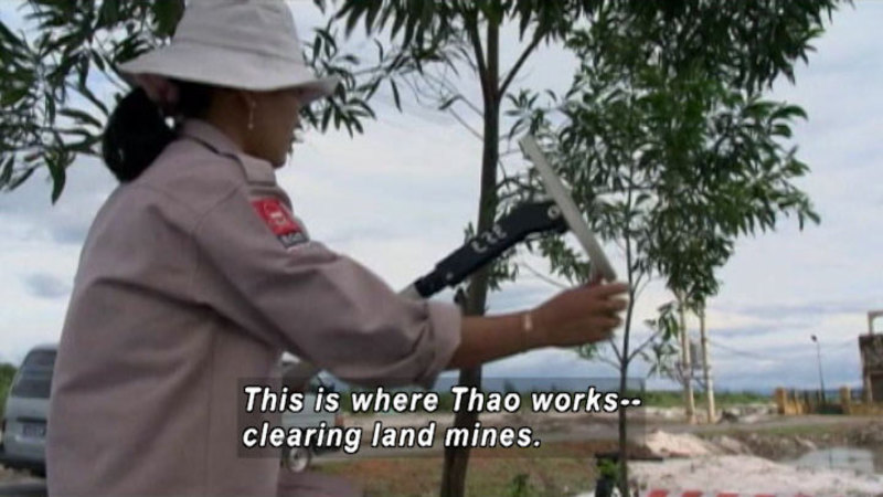 Person wearing khaki hat and shirt holding a tool. Low building and vehicle in background. Caption: this is where Thao works -- clearing land mines.