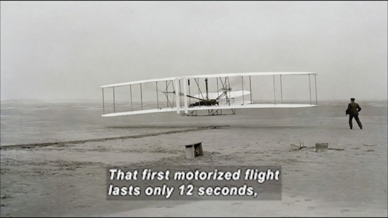 Black and white photograph of an early plane with a person standing next to it. Caption: That first motorized flight lasts only 12 seconds,