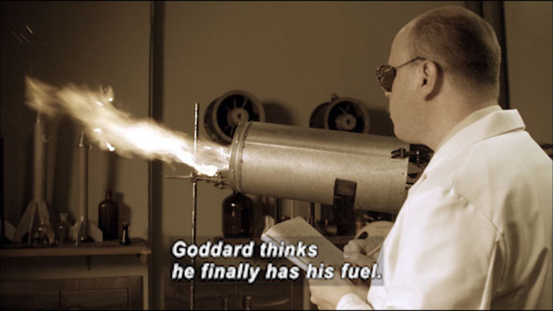 A man watching fire come out of a cylinder. Caption: Goddard thinks he finally has his fuel.