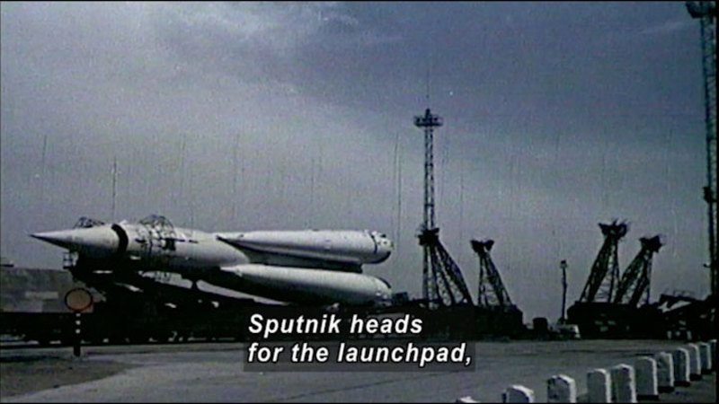 Black and white photograph of a rocket-like object on its side in an industrial area. Caption: Sputnik heads for the launchpad,