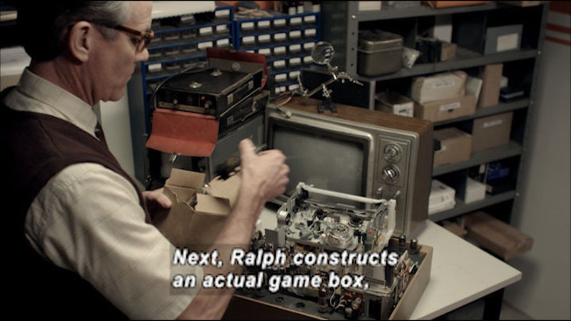 Person with a complex arrangement of wires and electronics partially assembled. Caption: Next, Ralph constructs an actual game box,