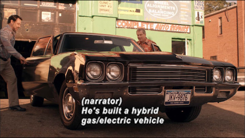 Two people getting into the passenger and driver side of a black vehicle. Caption: (narrator) He's built a hybrid gas/electric vehicle