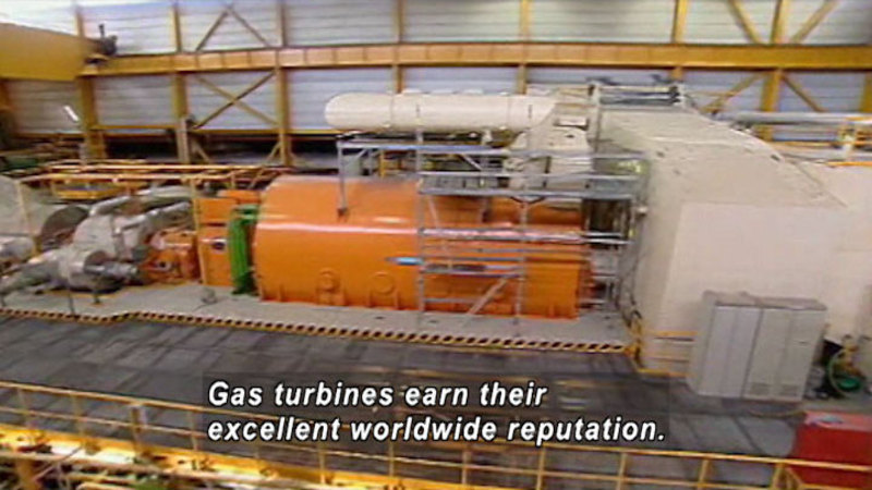 A large cylindrical machine set into the floor with various equipment attached to the round openings at either end. A walkway surrounds the mass of equipment. Caption: Gas turbines earn their excellent worldwide reputation.