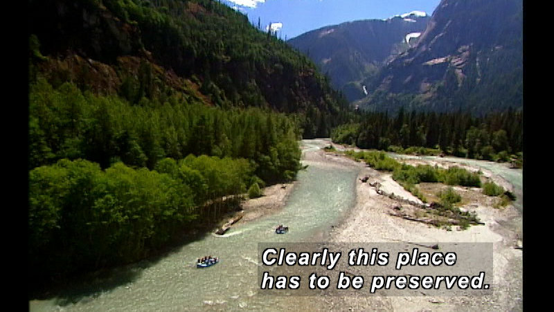 Tall snowcapped mountains covered in lush green trees and a light green river with two rafts winding through the valley. Caption: Clearly this place has to be preserved.