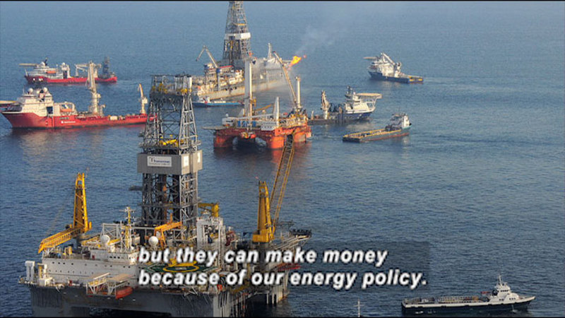 Oil drilling platforms in the ocean with many ships in the water around them. Caption: but they can make money because of our energy policy.