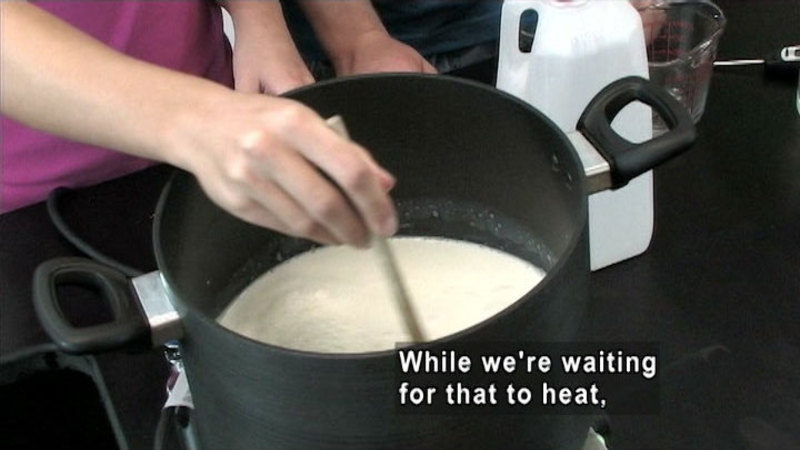 Person stirring a white liquid in a large pot. Caption: While we're waiting for that to heat,