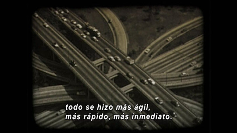Multiple levels of freeway on and off ramps with vehicles. Spanish captions.