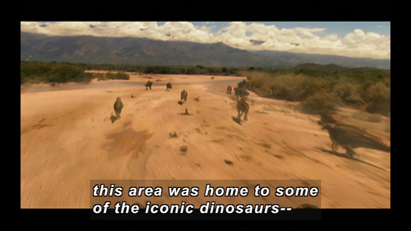 Dinosaurs running across a sandy expanse bordered by low trees. Caption: This area was home to some of the iconic dinosaurs --