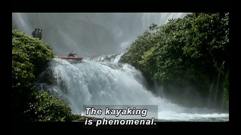 A kayak is about to go over a small waterfall on a river lined by lush greenery. Caption: The kayaking is phenomenal.