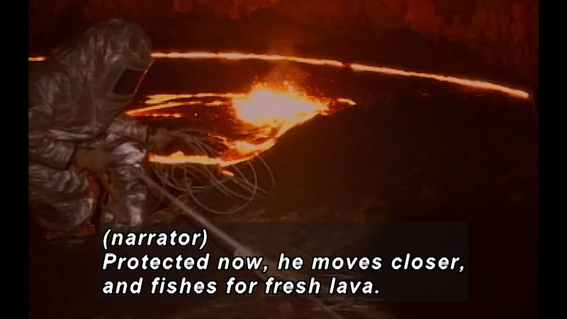 Person in a reflective heat-protecting suit crouches next to a pit of glowing lava. Caption: (narrator) Protected now, he moves closer and fishes for fresh lava.