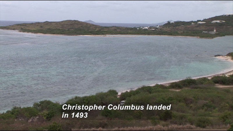 A protected bay of light green water with a handful of buildings slightly set back from the coastline. Caption: Christopher Columbus landed in 1493