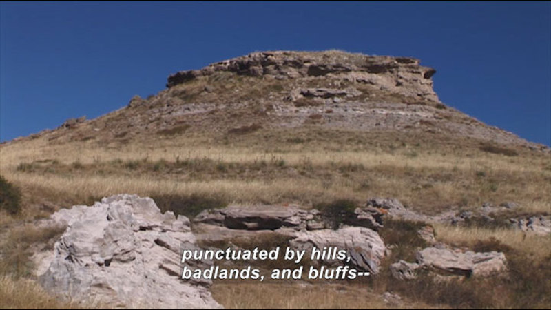 Dry, brown grass and brush with crumbling rocks throughout and a flat-topped rocky hill in the background. Caption: punctuated by hills, badlands, and bluffs --