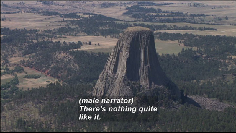 Rock formation rises sharply from evergreen tree covered ground to end in a narrowed flat-topped peak. Caption: (male narrator) There's nothing quite like it.