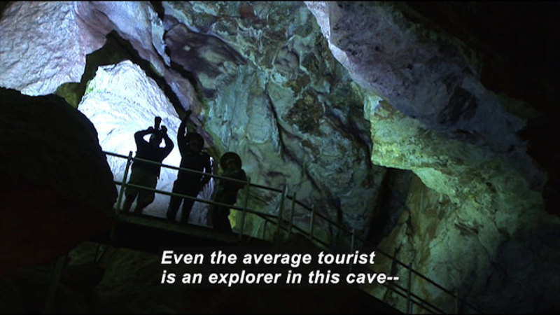 People standing on an overlook in a cave. Caption: Even the average tourist is an explorer in this cave--