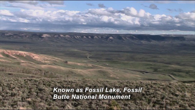 Rolling hills lead into a wide valley. Caption: Known as Fossil Lake, Fossil Butte National Monument